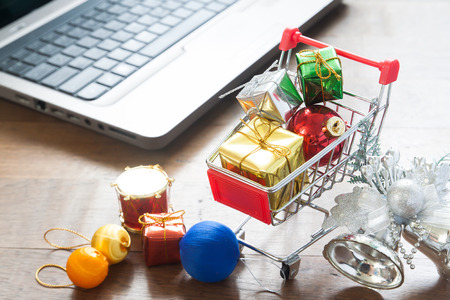 Gift boxes in shopping cart and Christmas decorations with laptop computer on wood table, Online shopping