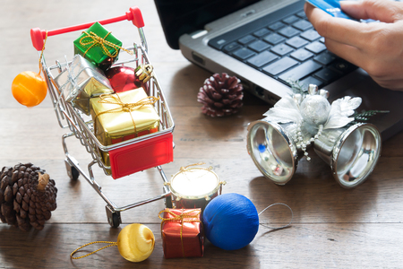 Gift boxes in shopping cart and Christmas decorations, Woman holding credit card on laptop computer for online shopping Stock Photo