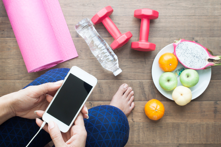 Healthy woman using smartphone before workout and yoga, Sport equipments, water and fruits on the floor