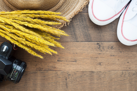 Creative flat lay of Autumn concept with dried flowers, camera, straw hat and sneakers on wood background