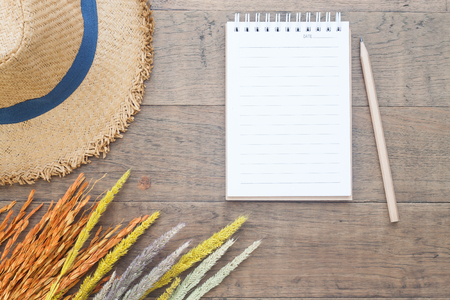Creative flat lay of Autumn and Fall concept, Dried flowers, straw hat and blank notebook with pencil on wooden background