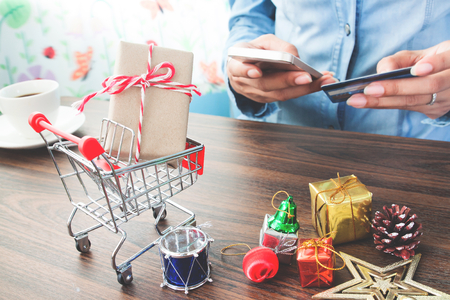 Shopping cart and gift boxes with hands holding credit card and using mobile phone, Online shopping for Christmas Stock Photo