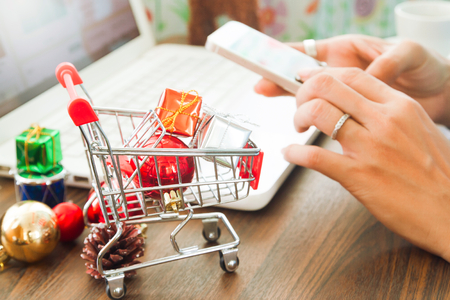 Online payment, Close up at gift boxes in shopping cart and Christmas decoration, woman hands using smartphone and laptop computer in background