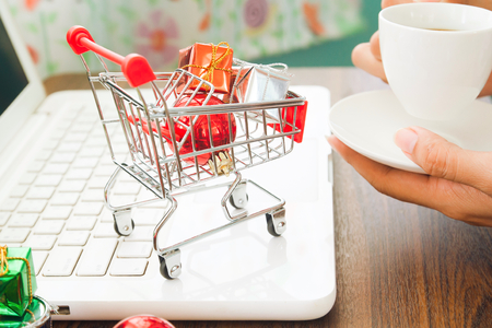 Christmas decorations and gift boxes in shopping cart on laptop, Online shopping concept