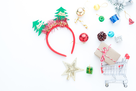 Christmas accessories and shopping cart with gift boxes on white background