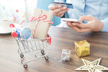 Craft gift box in shopping cart and Christmas gift with woman holding mobile phone and credit card, Online payment