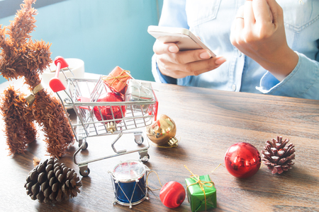 Gift boxes in shopping cart and Christmas decorations on table, Woman using mobile device, Online shopping concept Stock Photo