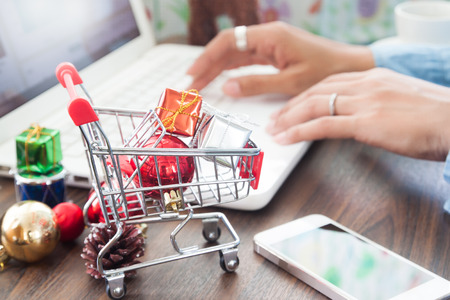 Gift boxes in shopping cart and Christmas decorations on table, Woman using laptop in background, Online shopping concept Stock Photo