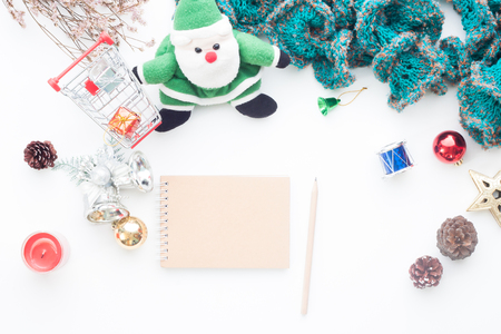 Blank notebook and pencil on white table with Christmas decorations and shopping cart, Top view Stock Photo