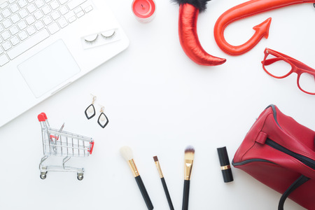 Creative flat lay of Halloween and fashion concept with laptop and shopping cart on white background, Online shopping
