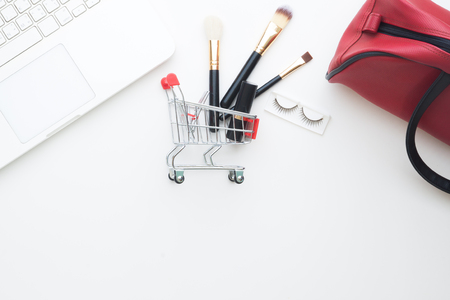 Beauty items and cosmetics in shopping cart with laptop computer on white background, Online shopping Stock Photo