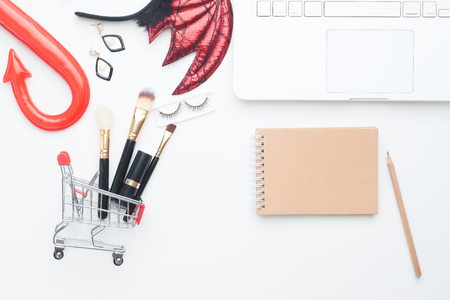 Beauty items in shopping cart with Halloween costume, Laptop computer and notebook with copy space, Online shopping and Halloween concept Stock Photo