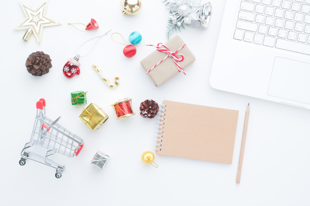 Shopping cart and Christmas decorations on white background with laptop computer and empty notebook, Top view