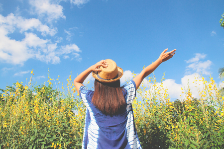 Back of happy woman in casual style with yellow flowers field and blue sky