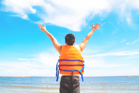 Asian man in life jacket hands up, Happy travel, Freedom and journey lifestyle concept