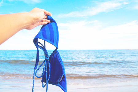 Woman hand holding bikini with sea and blue sky in background, Happy vacation Imagens