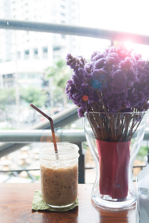 A glass of iced coffee with violet flowers, Lifestyle living Stock Photo