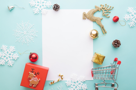 Creative flat lay of Gift box and ornaments with blank paper for text on pastel color background, Merry Christmas and Happy New Year concept