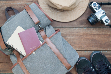 Travel and journey concept, Man's items with passport, notebook and camera on wooden background