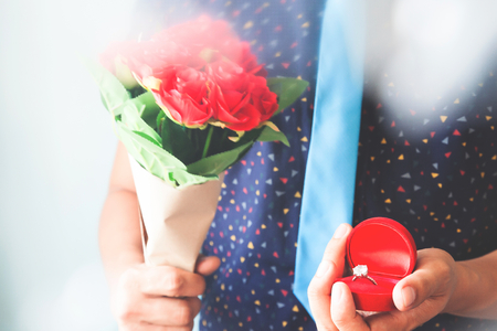 Close up man in casual shirt and necktie holding diamond ring and roses bouquet 写真素材
