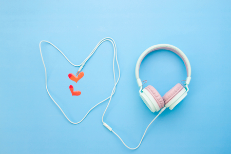 Pastel color headphone heart shape with little red heart on blue color background, Love emotion Stock Photo