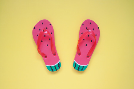 Flat lay of fashion sandals, watermelon on yellow color background