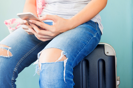 Traveler using smart phone, Close up woman's hands using mobile and sitting on luggage suitcase, Travel concept