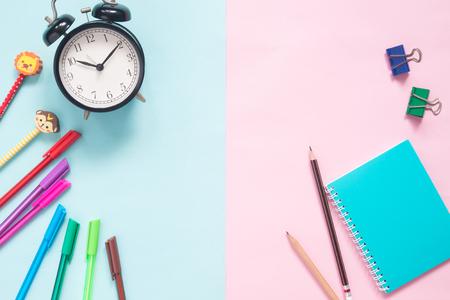 Vista superior del espacio de trabajo para niños, reloj despertador, lápices de colores, bolígrafos, cuaderno y clips sobre fondo de colores pastel Foto de archivo