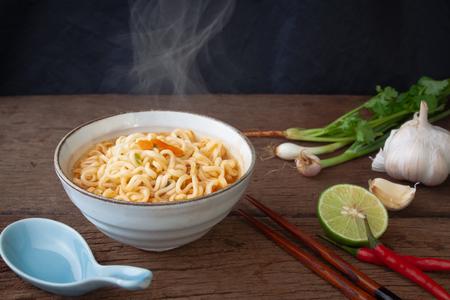 Instant noedels en ingrediënten, limoen, knoflook, chili en ui op houten tafel Stockfoto