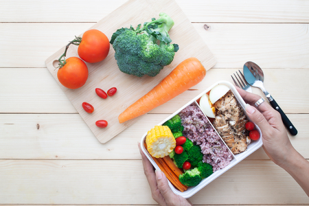 Vue de dessus des mains de femme tenant une boîte à lunch saine avec du poulet et des légumes, une alimentation saine, un repas nutritionnel Banque d'images