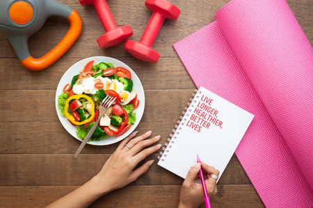 Woman writing on notebook with salad and fitness equipments on wooden table, Healthy living and beauty concept