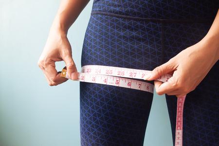 Close up woman hands measuring her legs Reklamní fotografie