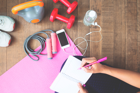Top view of sporty woman writing on notebook, planning workout