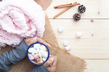 Woman hands with hot chocolate with pastel colour marshmallows on top. Cozy lifestyle. Winter concept