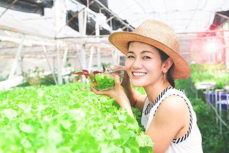 Young beautiful healthy woman holding salad bowl in organic vegetables farm Stock Photo