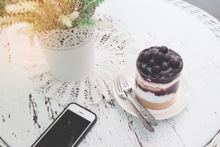 Blueberries short cake on vintage style table with mobile phone. Lifestyle concept 写真素材