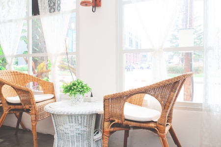Vintage style furniture made from rattan in cafe. Decorated in white color tone