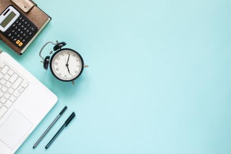 Creatief plat leggen van werkruimtebureau met laptop, caculator en notitieboekje op blauwe kleurenachtergrond. Bedrijfs-, verzekerings- of geldconcept