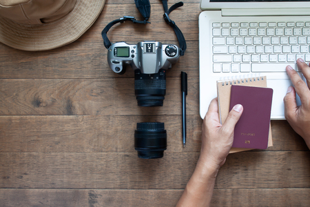 Overhead view of man hands using laptop and holding passport and camera on wooden background