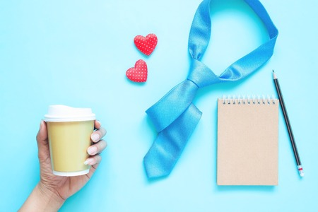 Creative flat lay of Father's Day concept. Necktie, notebook and woman hand holding coffee cup on pastel colour background