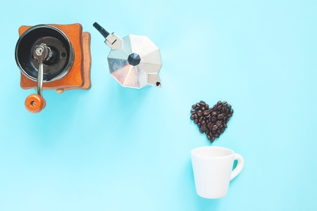 Creative flat lay of heart shape coffee beans and coffee grinder and pot on blue colour background