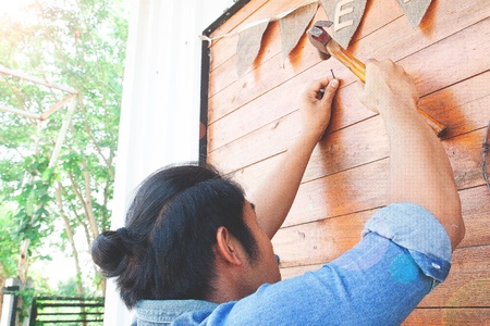 Asian man nailing wooden wall. Home improvement concept
