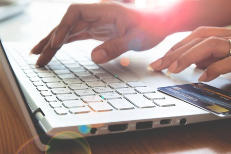 Nahaufnahme der Frau Hände mit Laptop-Computer und Kreditkarte. Online-Banking, Online-Shopping und E-Payment