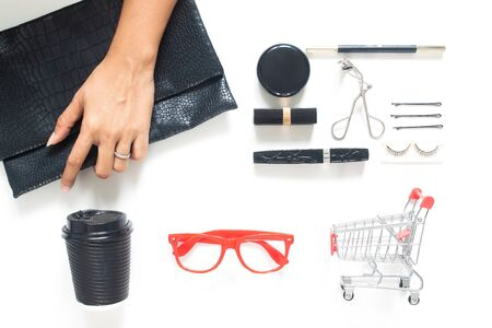 Woman hand holding trendy purse with woman accessories and cosmetics on white background. Beauty or Business concept
