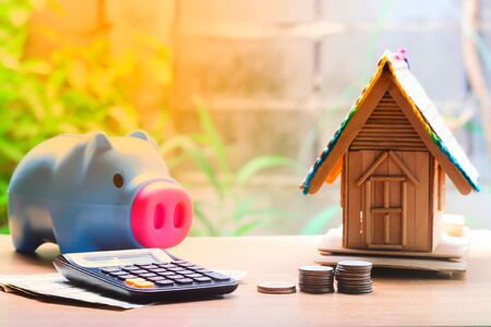 Coin stacks, house model, calculator and piggy bank, savings plans for housing