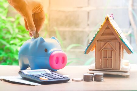 Woman hand put coin in piggy bank with coin stacks and house model, savings plans for housing