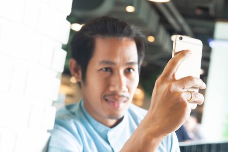 Hipster man calling by face time using smartphone. Smart life and technology concept. Focus on smartphone