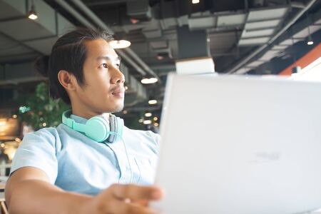 Handsome asian man using laptop looking out of window. Startup business concept
