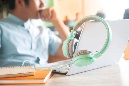 Pastel colour headphones, laptop computer and notebooks on workspace desk with handsome man on background. Working space. Technology concept Фото со стока