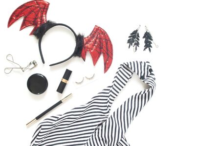 Creative flat lay of woman dress and accessories for Halloween party on white background with copy space.